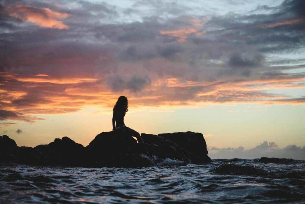 A mermaid sitting on a rock by the coast